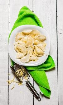 Ravioli freschi con formaggio nel piatto. su un tavolo di legno bianco. vista dall'alto