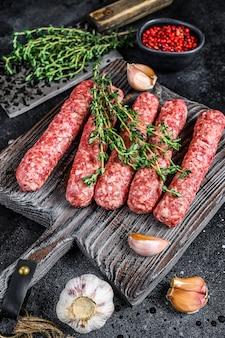 Spiedini di carne di manzo crudo fresco salsicce su un tagliere
