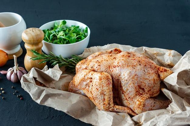 Pollo crudo fresco su carta da forno e spezie per cucinare.