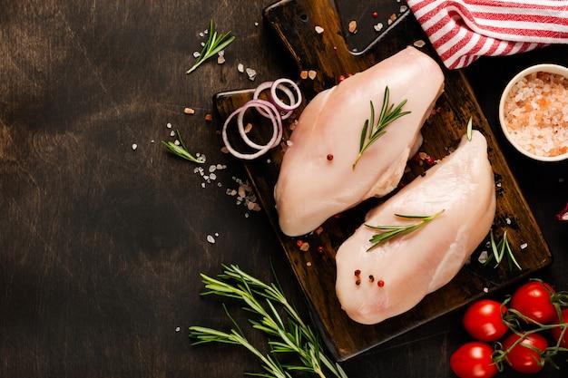 Filetto di carne di pollo crudo fresco con sale, pepe, cipolla su un fondo rustico di legno