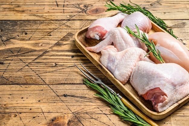 Carne di pollo crudo fresco, ali, petto, coscia e cosce su un vassoio di legno.