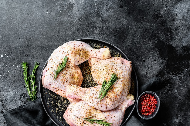 Cosce di pollo crudo fresco, gambe su un tagliere con spezie, cucina. sfondo nero
