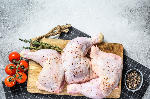 Cosce di pollo crudo fresco, gambe su un tagliere con spezie, cucina. sfondo grigio