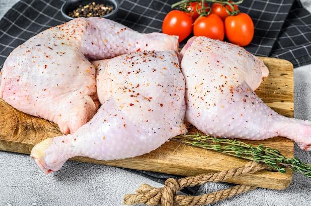 Cosce di pollo crude fresche, gambe su un tagliere con spezie, cottura.