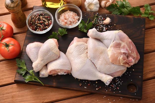Cosce di pollo crude fresche con ingredienti per cucinare su un tagliere di legno