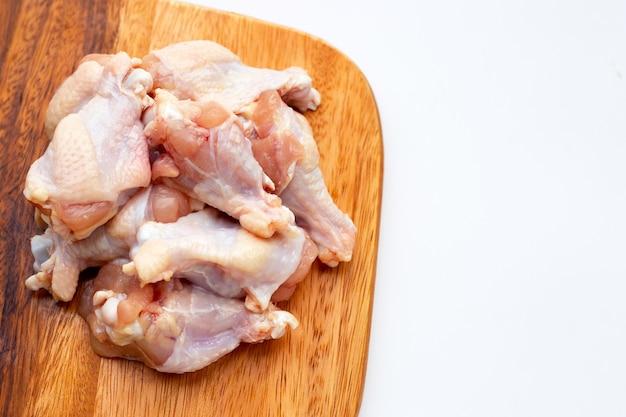 Ali di pollo crude fresche (wingstick) sul tagliere su fondo bianco.
