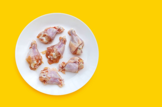 Ali di pollo crude fresche (wingstick) in piatto bianco su fondo giallo.