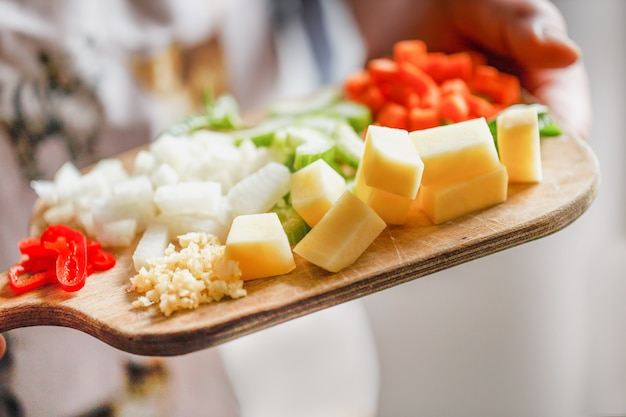 Verdure tritate crude fresche per cucinare la zuppa sulla tavola di legno in mani umane ravvicinate