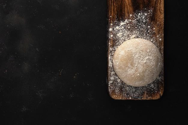 Pasta cruda fresca per pane o pizza su un fondo di legno rustico con una spolverata di farina.