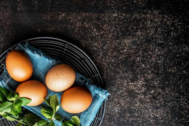 Uova fresche crude e foglie di basilico
