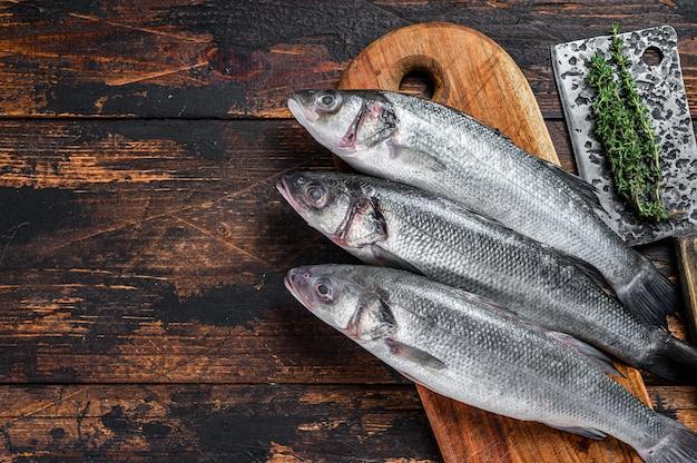 Spigola di pesce crudo fresco su un tagliere. fondo in legno scuro. vista dall'alto. copia spazio.