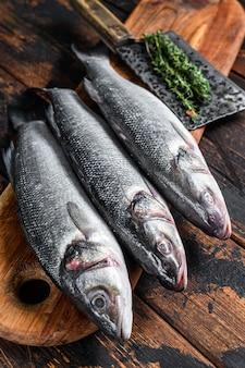 Spigola di pesce crudo fresco su un tagliere. fondo in legno scuro. vista dall'alto.
