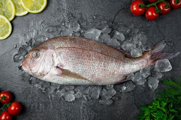 Pesce crudo fresco con limone, erbe aromatiche, olio d'oliva, su uno sfondo di pietra scura.