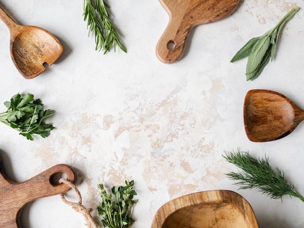 Erbe crude fresche e cucina in legno erano cornice su uno sfondo con texture. vista dall'alto, copia spazio.