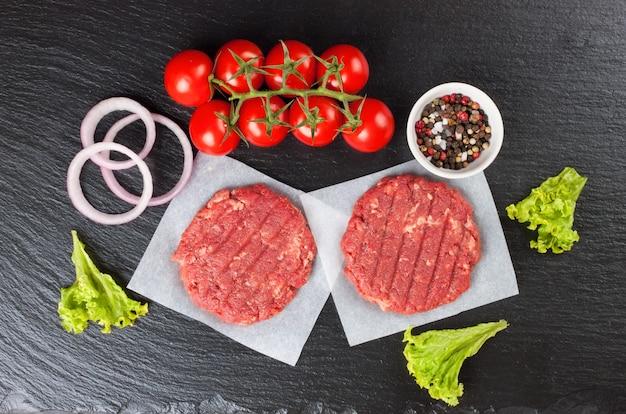 Hamburger di bistecca di manzo tritato fresco crudo fatto in casa con spezie, pomodori e insalata su un tavolo in ardesia nera, vista dall'alto. lay piatto.