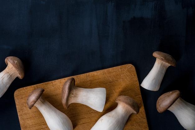Re crudo fresco, funghi ostrica reale sulla tavola di legno scuro