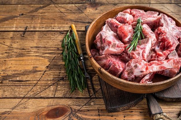 Carne cruda fresca con l'osso tagliata a dadini per gulasch in un piatto di legno