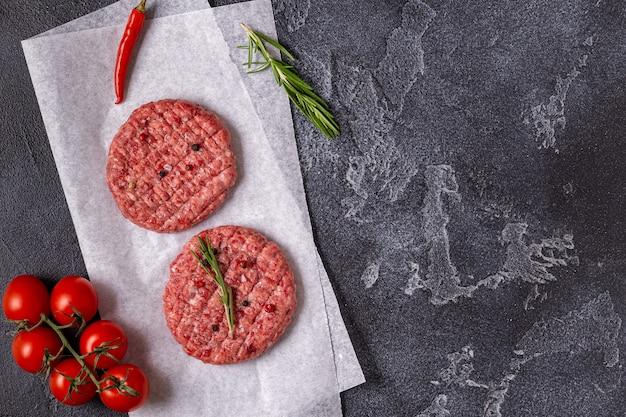 Cotoletta di hamburger di carne cruda fresca con erbe e spezie sulla tavola di pietra nera, vista dall'alto