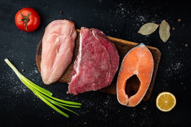 Carne cruda fresca, salmone e filetto di pollo su sfondo nero con spezie. alimento naturale ricco di proteine. vista dall'alto.