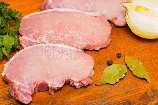 Carne cruda fresca con le spezie su fondo di legno