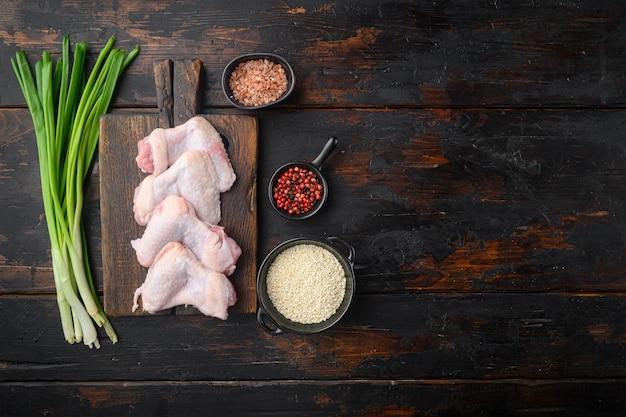 Ali di pollo medie crude fresche con set di ingredienti e sesamo, sul tagliere di legno, sul vecchio tavolo in legno scuro, vista dall'alto laici piatta