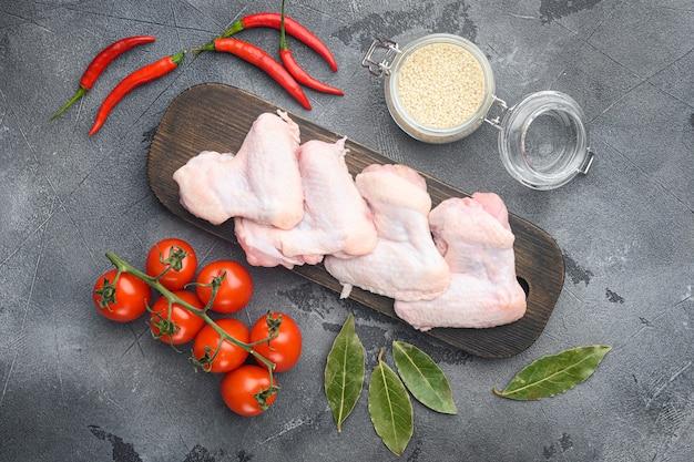 Ali di pollo medie crude fresche con l'insieme degli ingredienti e sesamo, sul tagliere di legno