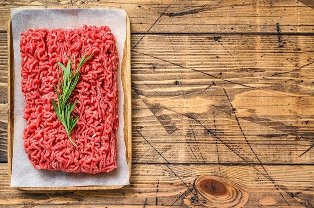 Carne di manzo crudo fresco, carne macinata su carta da macellaio.
