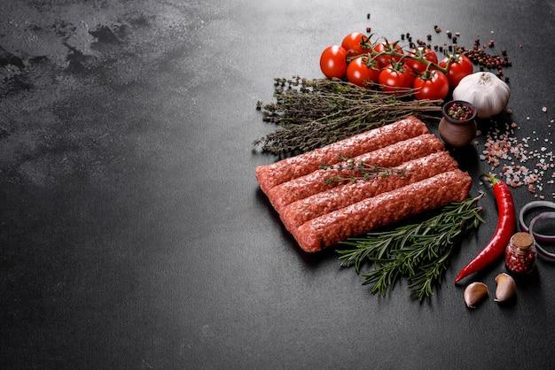 Tritare crudo fresco per kebab alla griglia con spezie ed erbe aromatiche su uno sfondo di cemento scuro