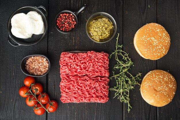 Carne di manzo tritata cruda fresca per hamburger di polpette con set di panini al sesamo, su tavolo di legno nero