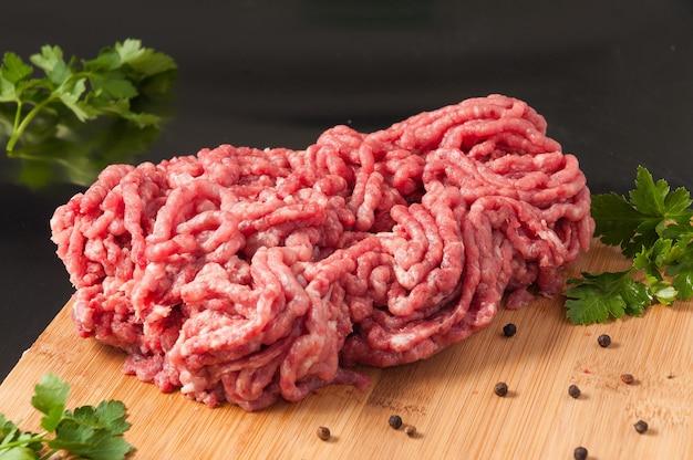 Carne di maiale tritata cruda fresca su una tavola di legno