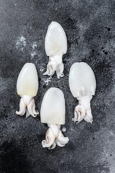 Mini seppie crude fresche sul tavolo. superficie nera. vista dall'alto. copia spazio