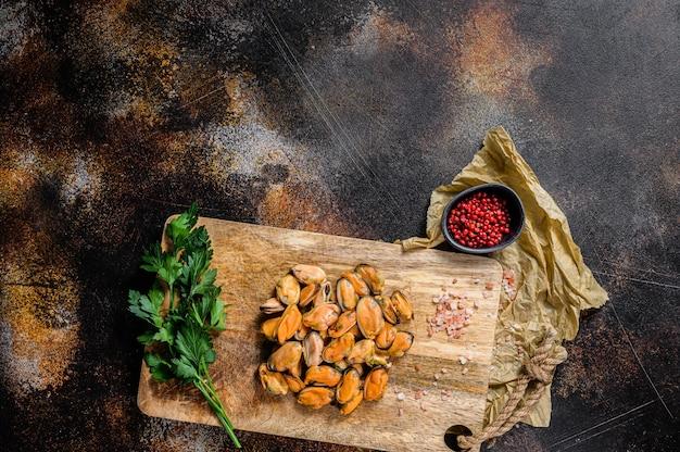 Carne di cozza cruda fresca su un tagliere di legno. frutti di mare sani. spazio per il testo.