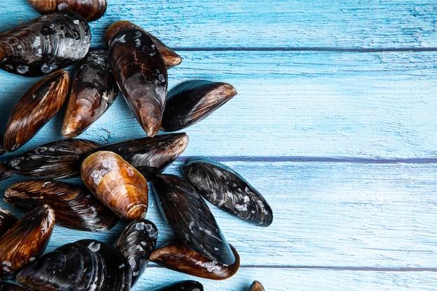 Cozze crude fresche su backgound di legno blu