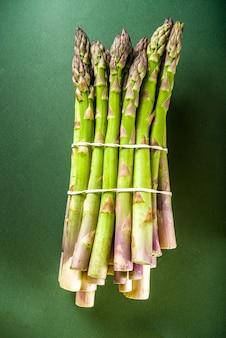 Mazzo di asparagi organici crudi freschi, verdura viola, verde e bianca su sfondo verde scuro