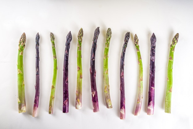 Mazzo organico crudo fresco dell'asparago, verdura porpora, verde e bianca su fondo bianco