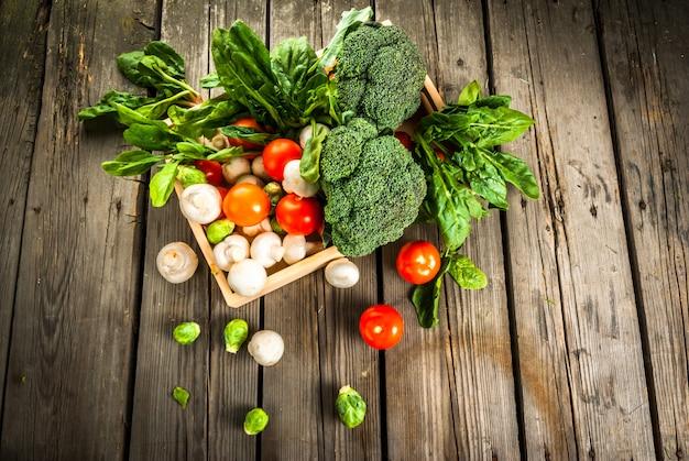 Verdure biologiche crude fresche su una tavola di legno rustica in cestino: spinaci, broccoli, cavoletti di bruxelles, pomodori, funghi, funghi prataioli.