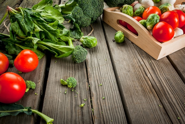 Verdure organiche crude fresche su una tavola di legno rustica