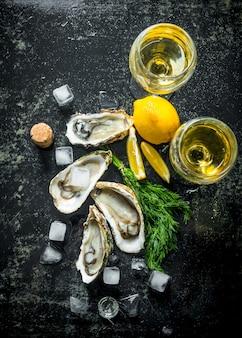 Ostriche crude fresche con cubetti di ghiaccio, aneto, limone e vino. sul tavolo rustico scuro