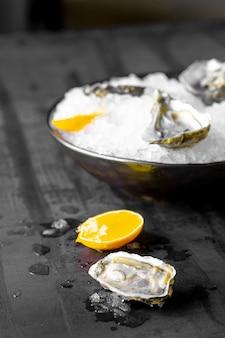 Ostriche crude fresche con ghiaccio e limone su fondo rustico scuro