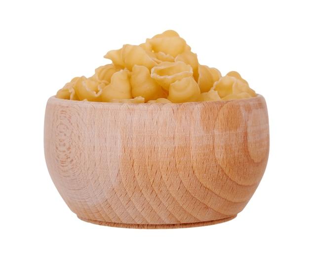 Pasta fresca cruda in ciotola di legno. isolato su uno spazio bianco.