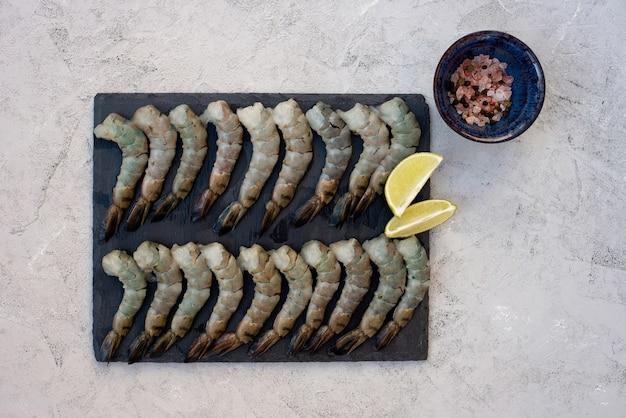 Gamberi sgusciati crudi freschi con spezie e limone su una tavola di pietra. i frutti di mare sani sono una fonte di proteine. disteso.