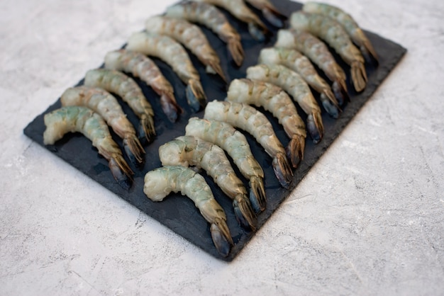 Gamberetto sbucciato crudo fresco su un bordo di pietra. i frutti di mare sani sono una fonte di proteine. disteso.