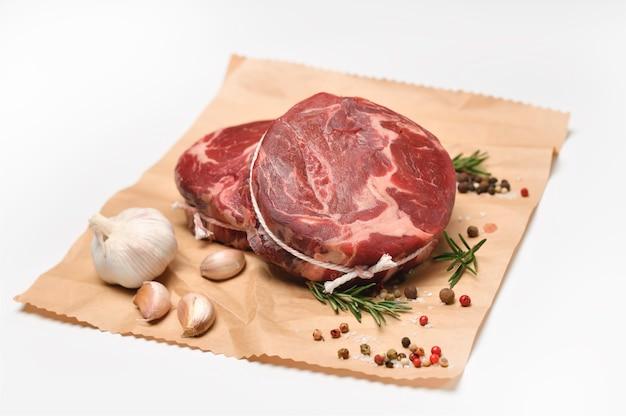 Pezzi crudi freschi di carne di manzo con ingredienti per la cottura su carta da imballaggio su superficie bianca