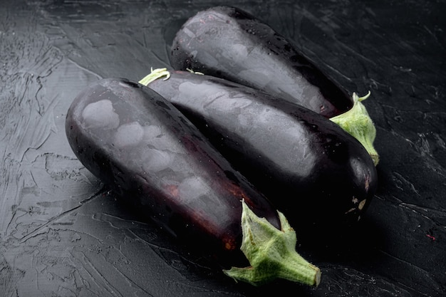 Set di melanzane viola crude fresche, su pietra nera