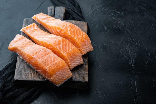 Tagli di filetto di salmone crudo fresco, su sfondo nero strutturato con spazio per il testo