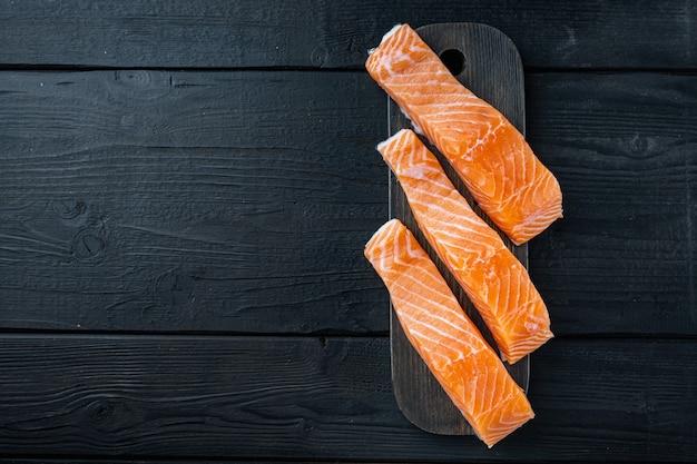 Tagli di filetto di salmone crudo fresco, sul tavolo di legno nero, piatto laici con spazio per il testo