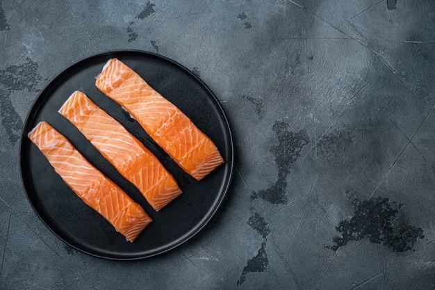 Tagli di filetto di salmone crudo fresco, su sfondo grigio, piatto laici con spazio per il testo