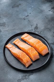 Tagli di filetto di salmone crudo fresco, su grigio