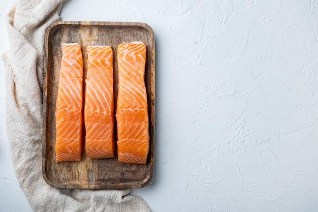 Tagli di filetto di salmone crudo fresco, su sfondo bianco strutturato, piatto con spazio per il testo