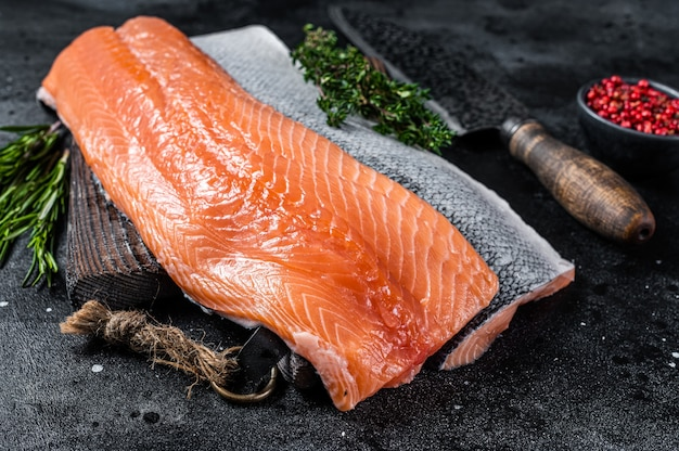 Filetto di salmone crudo fresco di pesce sul tagliere con coltello. sfondo nero.